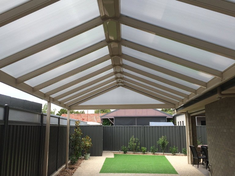 Carport with pitched roof and small garden