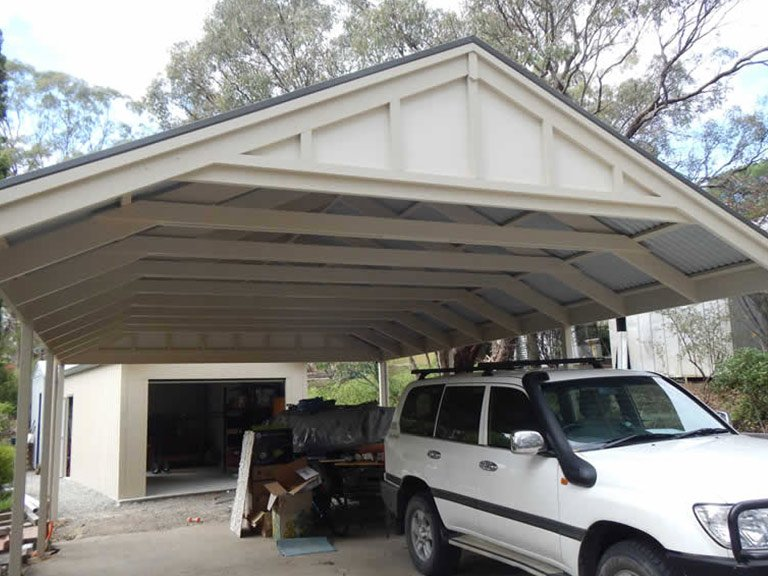 Large gabled timber carport with cars parked below