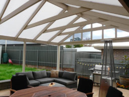 Large timber pergola shelters outdoor dining and BBQ